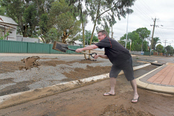 KGM-0029988 © WestPix Rain in Kalgoorlie-Boulder.  Picture: Mary Meagher. Leo Mannix shovelling dirt from his Robert Street property.