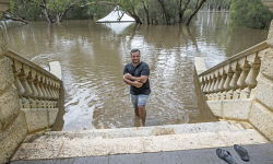 TWA-0063075 © WestPix Eric Lembo, owner of Caversham House, stands on the Grand Staircase which is three quarters under water; looking out to where the Hidden Garden is totally submerged. Picture: Steve Ferrier The West Australian.