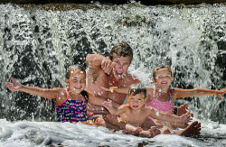 TWA-0064216 © WestPix Cooling off at Noble Falls, near Gidgegannup, Mark Moulton of Hillarys, with three of his four children, left to right, Hayley, six, Tom, two and Abbie, four. PICTURE: NIC ELLIS   THE WEST AUSTRALIAN