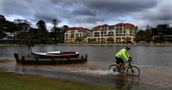 TWA-0071022 © WestPix Regular cyclist Paul Smale of Winthrop, cycles along a flooded pathway at Claisebrook Inlet in East Perth, after Perth received heavy rainfall overnight. PICTURE: NIC ELLIS    THE WEST AUSTRALIAN