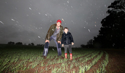 TWA-0071025 © WestPix Williams farmer Mark Fowler with five year old son Hugh enjoy the torrential rains finally falling on his oaten hay paddock. Picture: Sharon Smith The West Australian