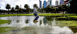 TWA-0073316 © WestPix Luke Whitehead jumps over the water flooded onto Langley Park in the city today.  Picture: Steve Ferrier The West Australian.