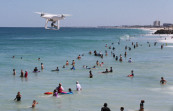 SUN-1401015 © WestPix Surf Life Saving WA trial of drones at Perth beaches. Pictured - The DJI Phantom 4, flies over CIty Beach just after it was evacuated due to a shark alarm. Picture: Daniel Wilkins