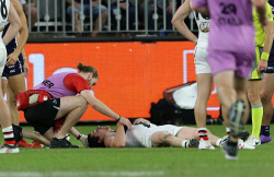 SUN-1405056 © WestPix AFL Round 8 - Fremantle Dockers vs St Kilda Saints at Optus Stadium, Perth. PIctured -  St Kilda's Jake Carlisle in the hands of the trainers after a head knock during the second term. Picture: Daniel Wilkins