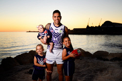 SUN-1405173 © WestPix Fremantle Docker Michael Walters (wearing Fremantle's white Indigenous Round jersey) and his daughters Addison, 4, Laila, 6, and 5 month old baby Makenzie, pictured at Bathers Beach Fremantle. Picture: Richard Hatherly