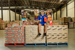 "TWA-0089903 © WestPix ""Meters for meals"". Andrew Gaff ran 14.9km during the Sunday match which is the equivalent of 7500 meals donated by AGL to Foodbank. Over the season it will represent 50000 meals. Pictured is Andrew Gaff from the West Coast Eagles with pallets of food equivalent to 7500 meals at Foodbank in Perth. Picture: Ross Swanborough. 21 May 2018."