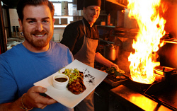 TWA-0093138 © WestPix Bevan Marwick, co-owner of The Vic in Subiaco, with the pub's five dollar steak, watched by chef Sean Morgan. PICTURE NIC ELLIS   THE WEST AUSTRALIAN