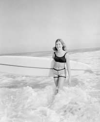 WAN-0031570 © WestPix SURF BOARD RIDER STEFANIE MEYER IS ENJOYING THE BIG SURF AT COTTESLOE BEACH. 8 AUGUST 1964.
