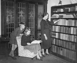 WAN-0031736 © WestPix PORTRAIT OF FORMER UNIVERSITY LECTURER MRS MAURICE JOHNSON, PRESIDENT OF A COMMITTEE TO RAISE FUNDS TO BUILD A RESIDENTIAL COLLEGE FOR WOMEN AT THE UNIVERSITY OF WESTERN AUSTRALIA, PICTURED AT BOOKCASE WITH HER CHILDREN, ANDREW JOHNSON AND SUSAN JOHNSON, IN AUGUST 1948